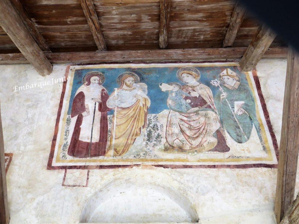 Afresco da Virgem com o Menino na fachada de Pieve di San Pietro di Feletto. Menino Jesus repousa sobre o colo da Virgem. Atrás dela, um Bispo e à sua frente Santo Antonio e São Tiago.
