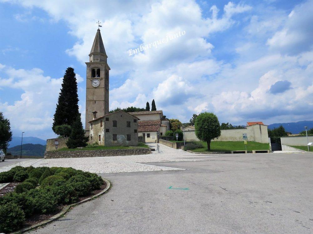 Praça da Pieve de San Pietro di Feletto. Na praça há a pequena igreja e sua torre em pedra. Um relógio redondo e um sino se destacam-se no alto da torre. Ao lado desta, um pinheiro bem alto.