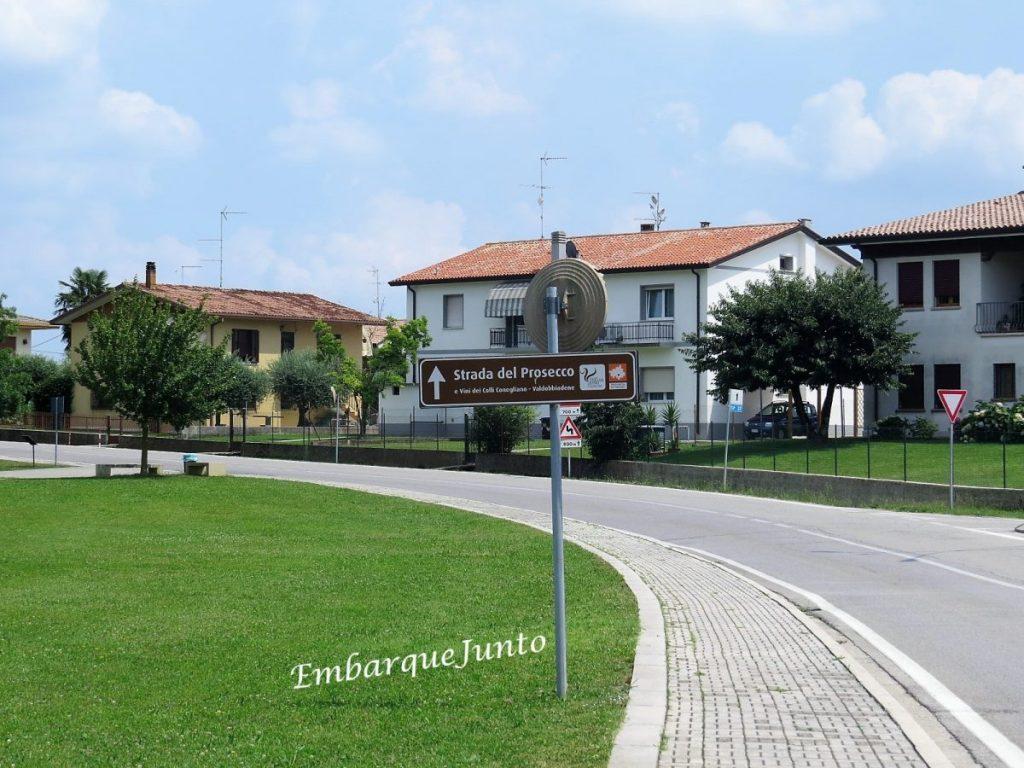 Estrada do Prosecco em San Pietro di Feletto. Pista asfaltada e em curva. Em um lado da pista há um gramado verde e do outro, residências.
